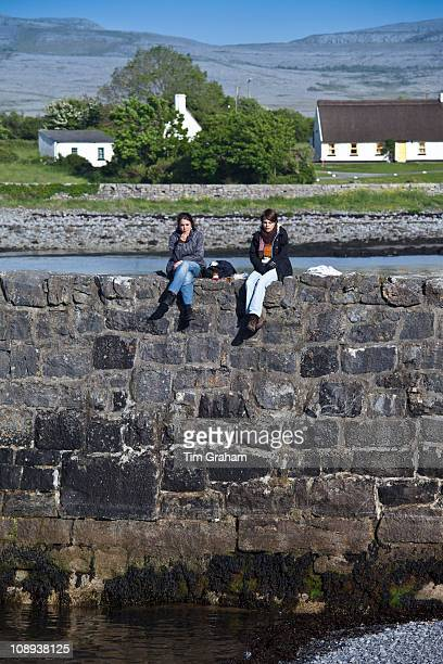 Tourists taking a lunch break on the pier sea defence wall at Ballyvaughan County Clare West Coast of Ireland