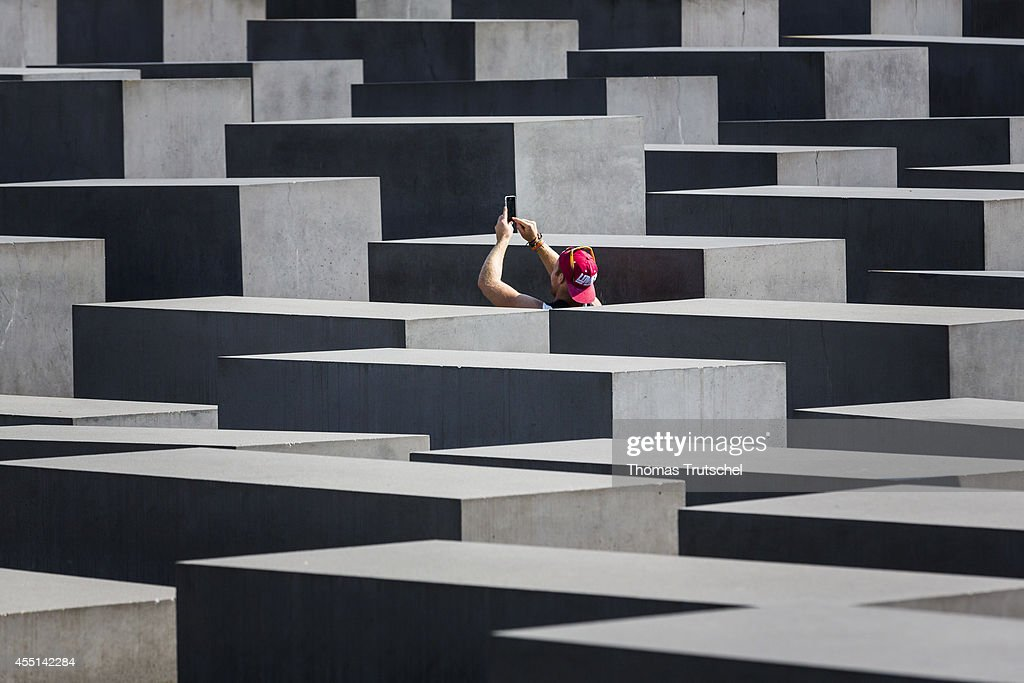 Tourists taking a photo of the concrete slabs stelae of the Memorial to the Murdered Jews of Europe on September 04 in Berlin Germany The monument is...
