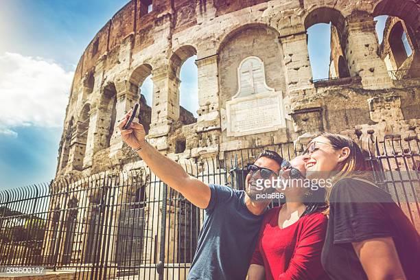 Touristes prenant un selfie devant le Colisée, Rome