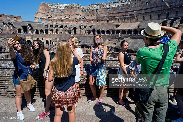 Tourists taking a selfie inside the Colosseum using a selfie stick extendable Large influx of Italian and foreign visitors to the Colosseum are about...