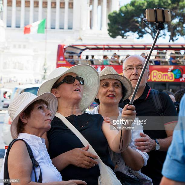 Tourists taking a selfie with selfie stick in Rome, Italy