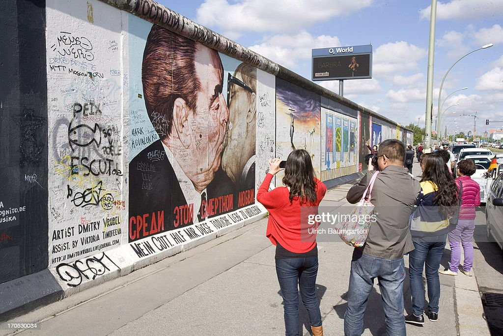 Tourists taking photos at the East-Side-Gallery in Berlin, an open air gallery on an old piece of the Berlin Wall, on May 27, 2013 in Berlin, Germany.