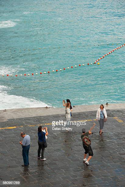 Tourists taking photos in wet conditions, Positano