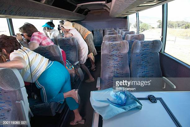 Tourists taking photos out of coach window, interior view