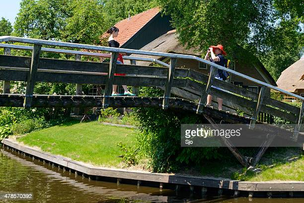 Tourists taking pictures on a bridge in Giethoorn