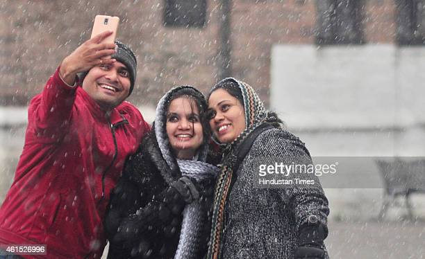 Tourists taking selfie during snowfall at the ridge on January 14 2015 in Shimla India Shimla and its surrounding resorts of Kufri Fagu and Narkanda...