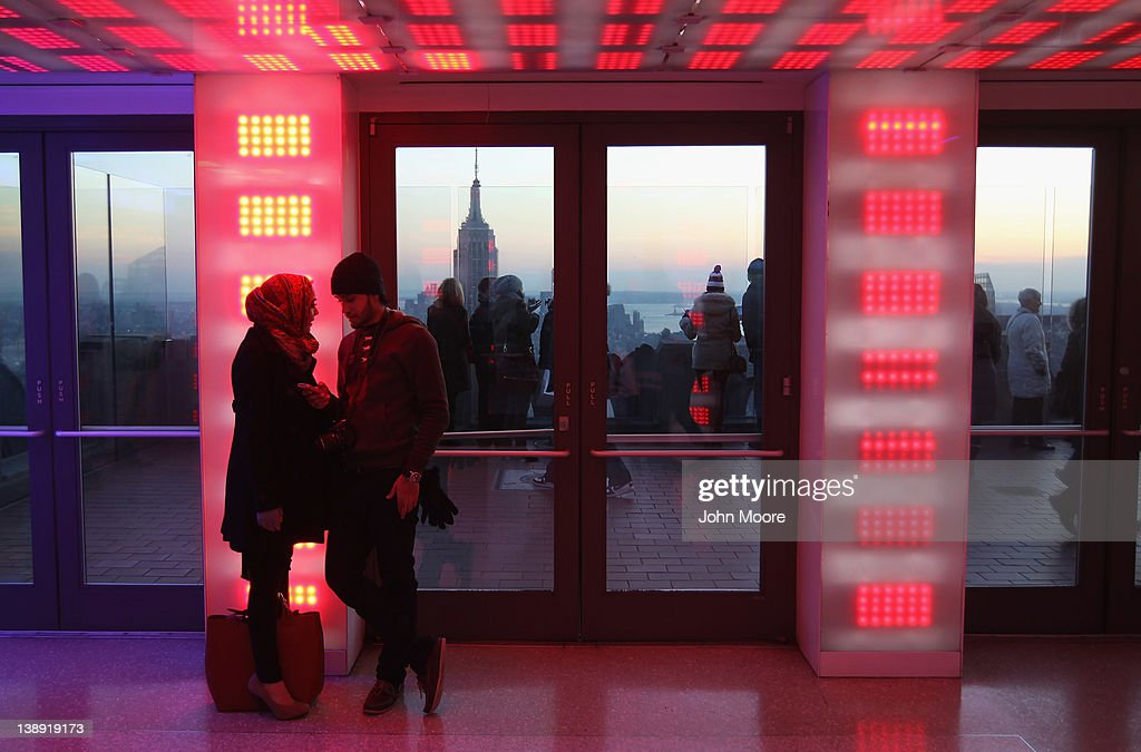 Tourists talk atop Rockefeller Center as the Empire State Building rises above the Manhattan skyline in the background on February 13, 2012 in New York City. The owner of the Empire State Building, Malkin Holdings, plans to raise up to $1 billion in an initial public offering on the 102 story Manhattan landmark.