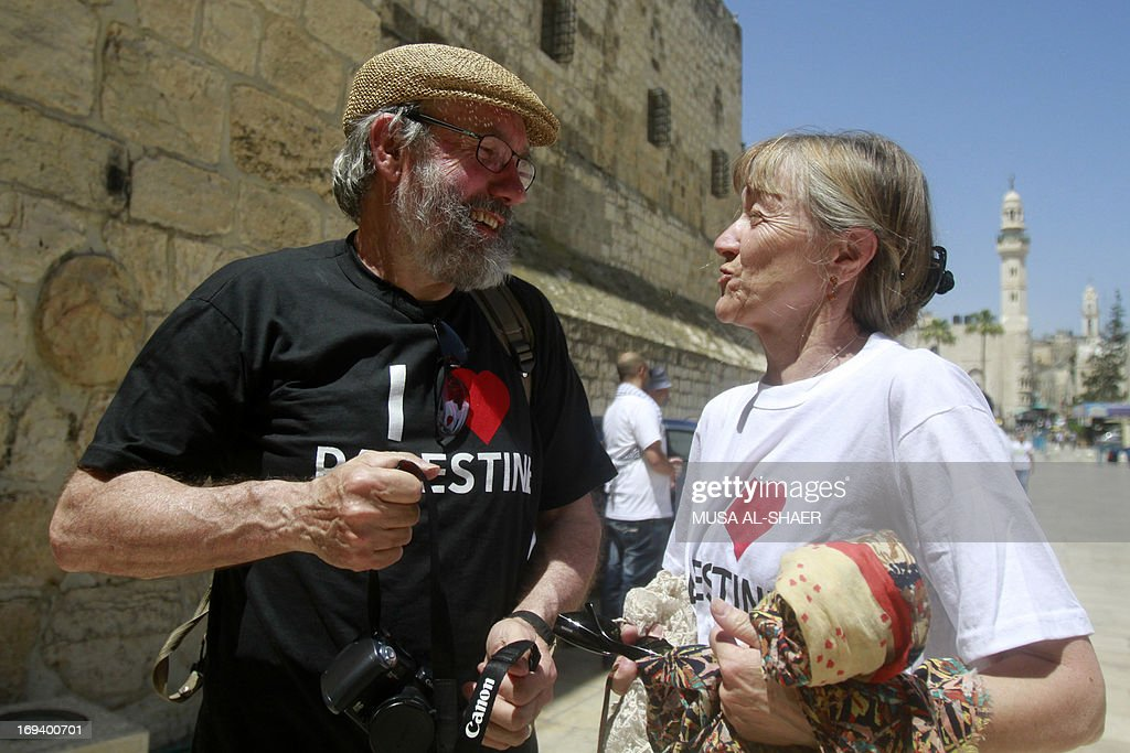 Tourists talk wearing T-shirts reading 'I love Palestine' that they were offered by Palestinian youths as part of a campaign to raise awareness among foreign visitors about Palestinian indentity on May 24, 2013 in front of the Church of the Nativity in the West bank town of Bethlehem. AFP PHOTO/MUSA AL SHAER