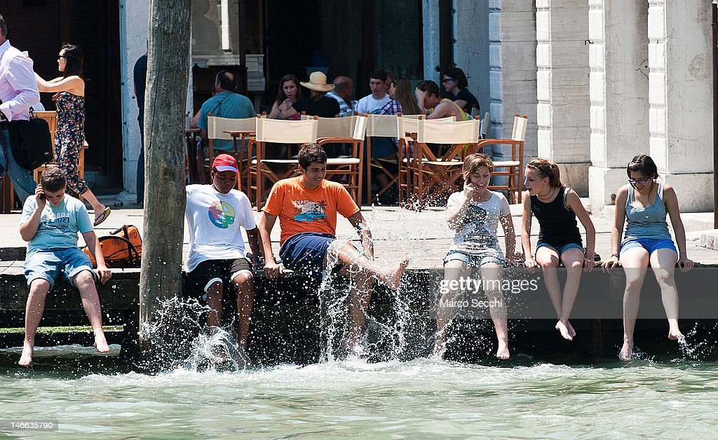 Tourists teenagers put their feet in the water of the Grand Canal on June 21, 2012 in Venice, Italy. An intense heatwave is sweeping across many regions in Italy, prompting the country's health ministry to issue a number of high level alerts.