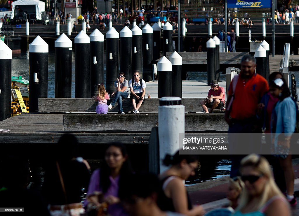 Tourists throng the waterfront along Sydney's Darling Harbour area on December 30, 2012. Darling Harbour, a bustling port and goods terminus some 50 years ago, was redeveloped and from 1988 to the present day attracts locals and tourists to its cafes, bars, entertainment centres and museums. AFP PHOTO/MANAN VATSYAYANA