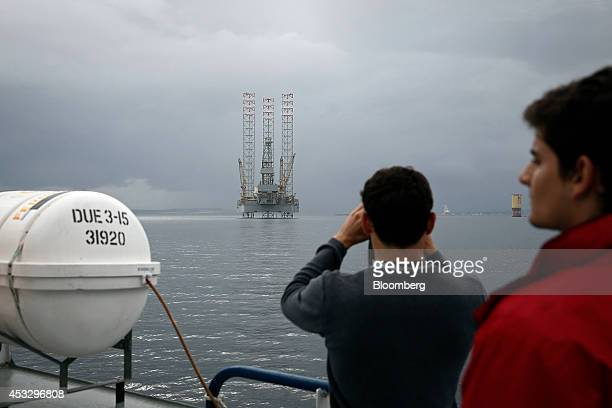 Tourists travel on the Cromarty ferry as it passes the anchored Prospector 1 offshore drill rig operated by Prospector Offshore Drilling SA in the...