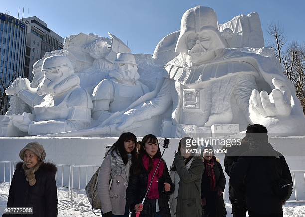 Tourists use a selfie monopod as they visit a large snow sculpture called the snow 'Star Wars' made by the Japan Ground SelfDefense Force Sapporo...
