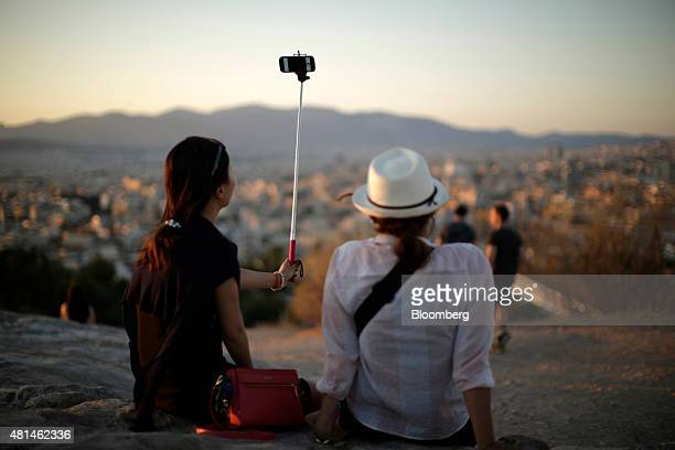 Tourists use a 'selfie' stick to photograph themselves against the backdrop of the Parthenon temple as they watch the sun set from Acropolis Hill in...
