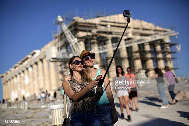 Tourists use a 'selfie' stick to photograph themselves against the backdrop of the Parthenon temple on Acropolis Hill in Athens Greece on Monday July...