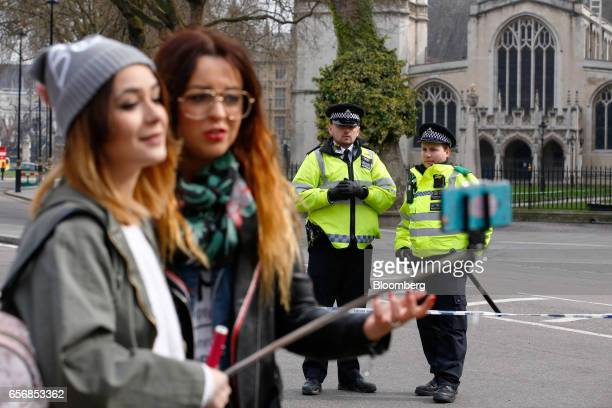 Tourists use a 'selfie' stick to take photos of themselves as police watch outside Westminster Abbey after the terror attack at Westminster in...