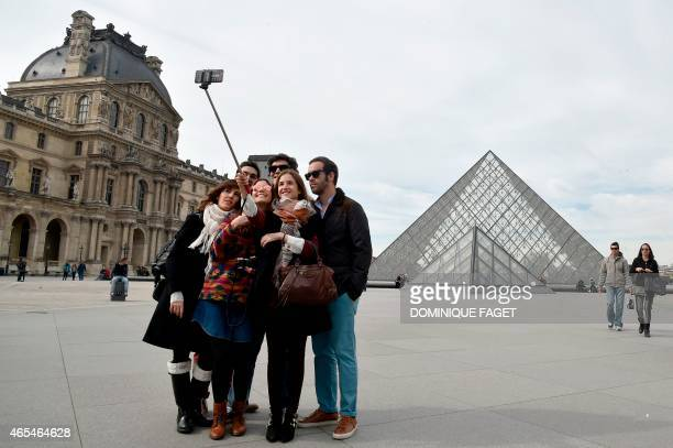 Tourists use a selfiestick to take a picture of themselves in front of the Pyramid of the Louvre in Paris on March 7 2015 AFP PHOTO / DOMINIQUE FAGET