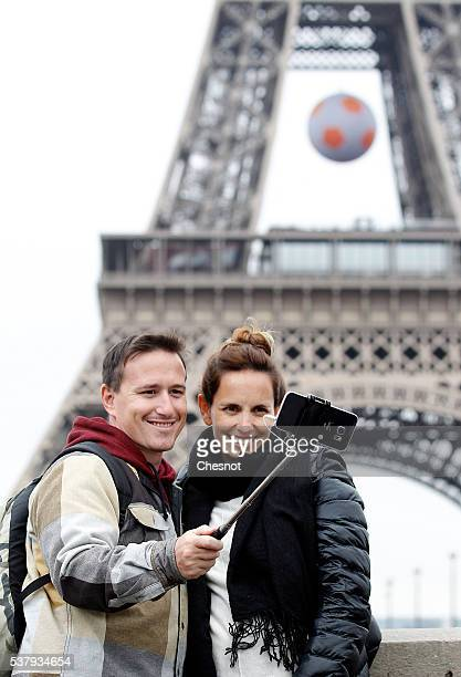 Tourists use a selfiestick to take a picture of themselves in front of the Eiffel tower decorated with a soccer ball for the the UEFA 2016 European...