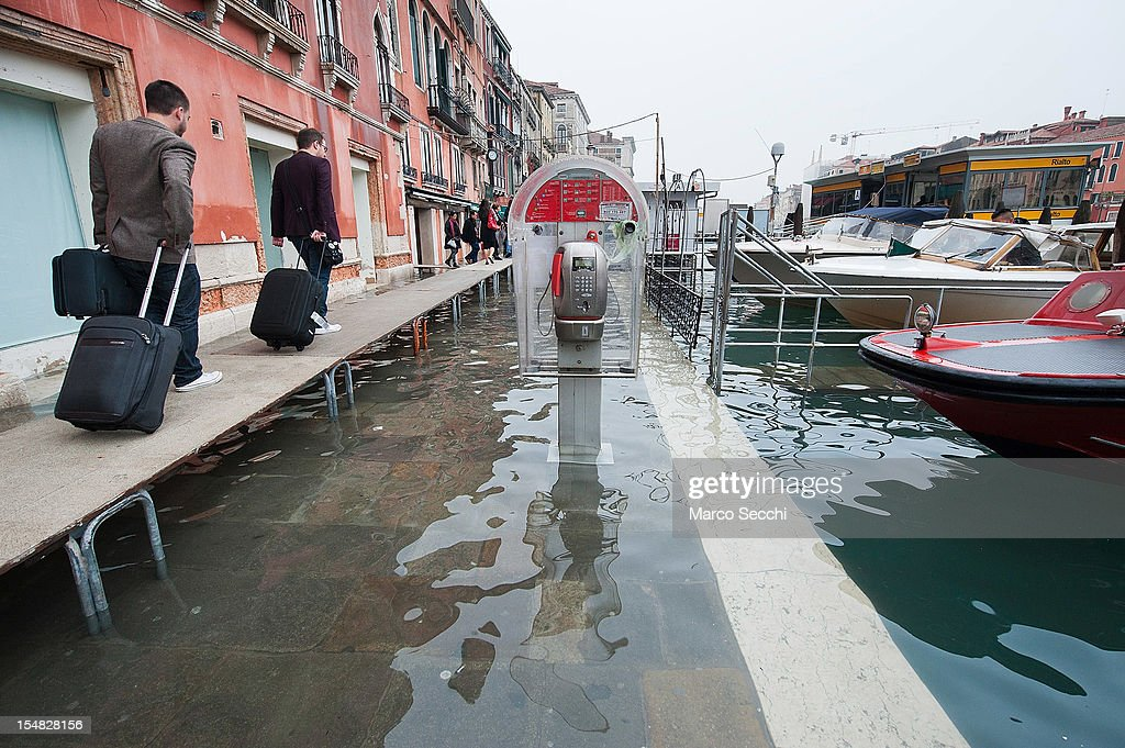 Tourists use the walkways near Rialto Bridge during today high tide on October 27, 2012 in Venice, Italy. The high tide, or acqua alta as it is locally known, stood at 127 centimeters this morning.