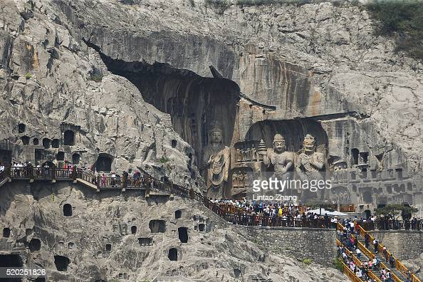 Tourists view Buddhist sculptures at Longmen Grottoes on April 10 2016 in the outskirts of Luoyang of Henan Province China Longmen Grottoes comprises...