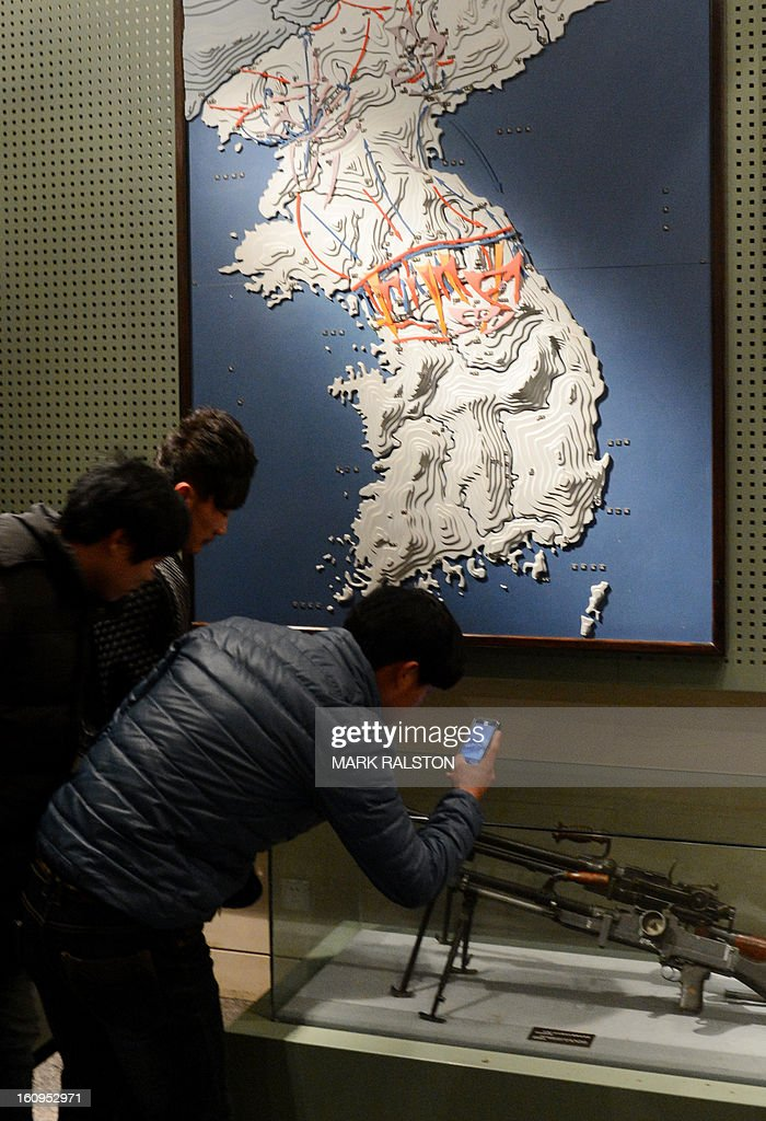 Tourists view guns and a Korean map at the 'Museum to Commemorate the War to Resist US Aggression' at the Chinese city of Dandong on February 8, 2013. US Secretary of State John Kerry warned that North Korea's expected nuclear tests only increase the risk of conflict and would do nothing to help the country's stricken people. The country has vowed to carry out a third nuclear test soon, and concerns have been raised over the type of fissile material used in the device. AFP PHOTO/Mark RALSTON