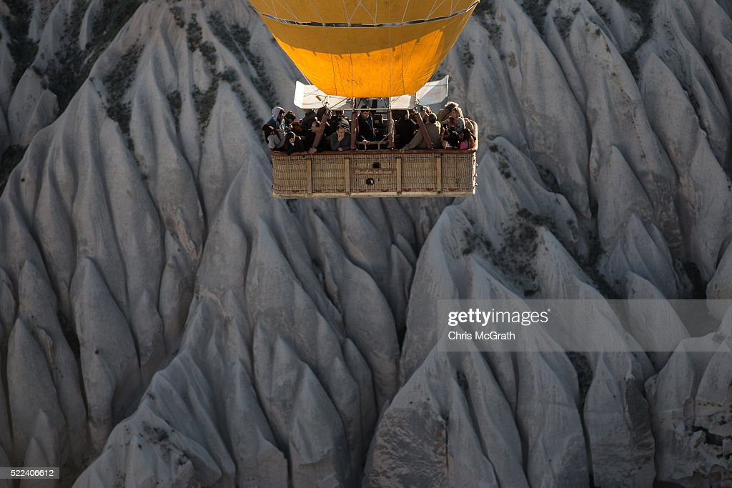 Tourists view rock formations during a hot air balloon tour on April 17, 2016 in Nevsehir, Turkey. Cappadocia, a historical region in Central Anatolia dating back to 3000 B.C is one of the most famous tourist sites in Turkey. Listed as a World Heritage Site in 1985, and known for its unique volcanic landscape, fairy chimneys, large network of underground dwellings and some of the best hot air ballooning in the world, Cappadocia is preparing for peak tourist season to begin in the first week of May. Despite Turkey's tourism downturn, due to the recent terrorist attacks, internal instability and tension with Russia, local vendors expect tourist numbers to be stable mainly due to the unique activities on offer and unlike other tourist areas in Turkey such as Antalya, which is popular with Russian tourists, Cappadocia caters to the huge Asian tourist market.