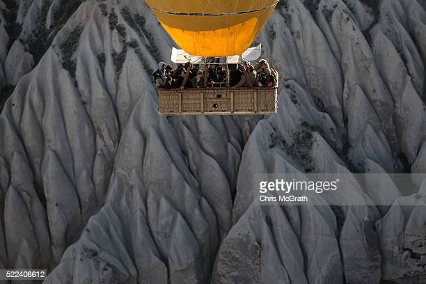 Tourists view rock formations during a hot air balloon tour on April 17 2016 in Nevsehir Turkey Cappadocia a historical region in Central Anatolia...
