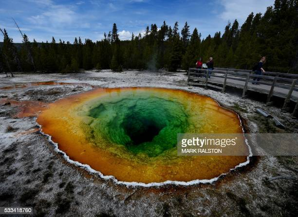 Tourists view the Morning Glory hot spring in the Upper Geyser Basin of Yellowstone National Park in Wyoming on May 14 2016 The distinctive colors of...