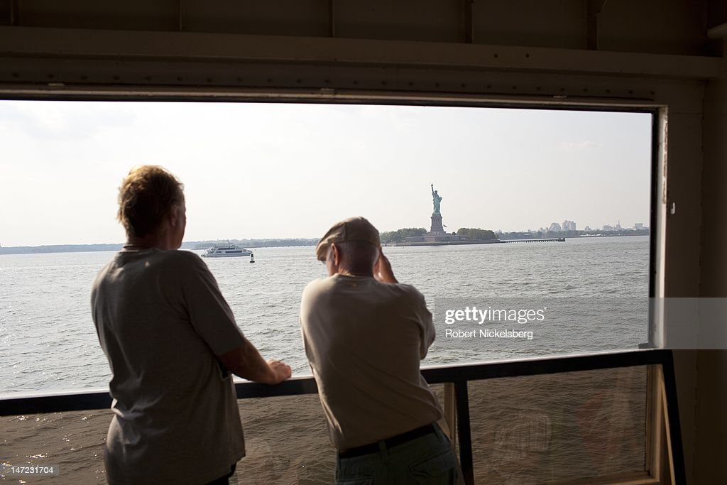 Tourists view the Statue of Liberty June 20, 2012 while riding the Staten Island Ferry in New York City.