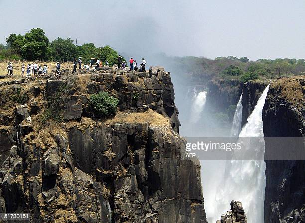 Tourists view the Victoria Falls in Livingstone Zambia where the 150th anniversary of the discovery of Victoria Falls by Scottish missionary David...