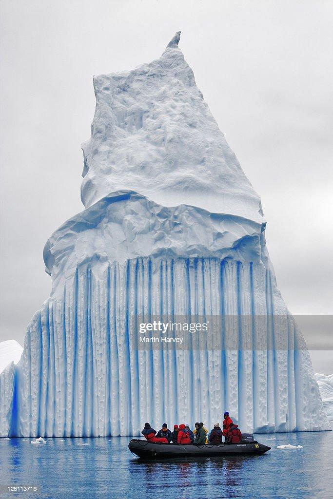 Tourists viewing iceberg from zodiac, Antarctica. : Stock Photo