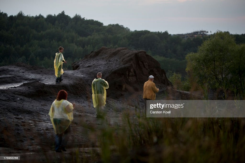 Tourists visit a brown coal opencast mine at dusk in the Welzow open-pit lignite coal mine on August 10, 2013 near Welzow, Germany. The mine, operated by Vattenfall, is one of several in the immediate area that feed a nearby power plant with coal. In a development project initiated by state government, other nearby former open-pit mines have been turned into lakes in a rejuvenation effort that is also intended to make the area a viable tourist destination.
