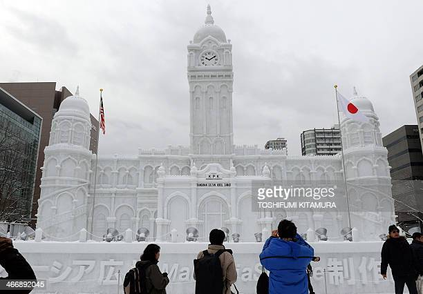 Tourists visit an 18metre high and 28metrewide snow statue of the Sultan Abdul Samad building at situated at Malaysia square during the 65th annual...