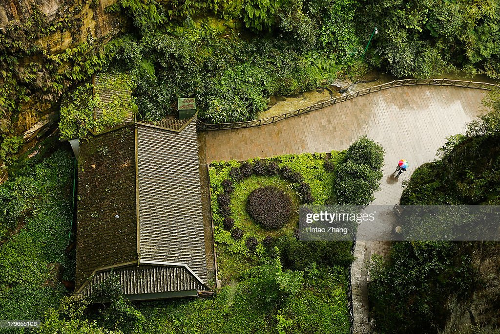 Tourists visit Baofeng Lake in the rain at Zhangjiajie national park on September 1 2013 in Zhangjiajie China Zhangjiajie National Forest park is a...