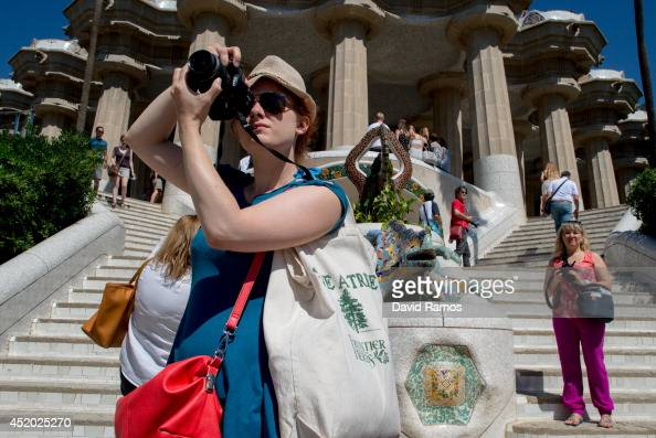 Tourists visit Gaudi's Park Guell on July 11 2014 in Barcelona Spain As traders of 'La Boqueria' complain about tour groups getting in the way of...