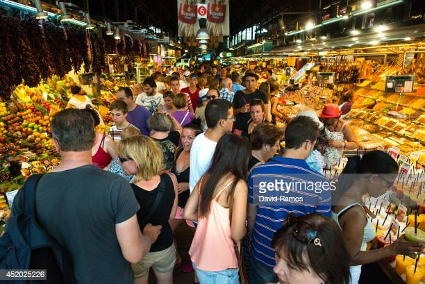 Tourists visit 'La Boqueria' green market on July 11 2014 in Barcelona Spain As traders of 'La Boqueria' complain about tour groups getting in the...