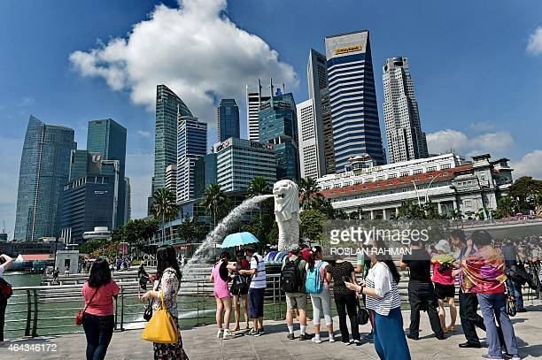 Tourists visit Singapore's famous Merlion in front of the skyline of the city's financial business district on February 25 2015 Singapore on February...