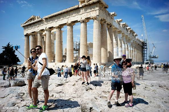 Tourists visit the ancient Acropolis hill with the ruins of the fifth century BC Parthenon temple on June 30 2015 in Athens Greece Greek voters will...