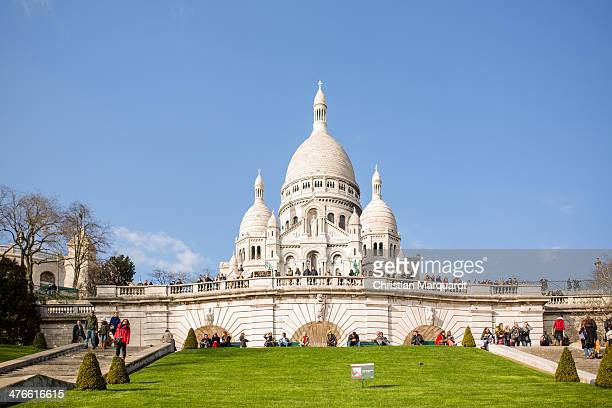 Tourists visit the Basilica SacreCoeur on a sunny day on March 1 2014 in Paris France SacreCoeur is located on a hill named Montmatre which is also...