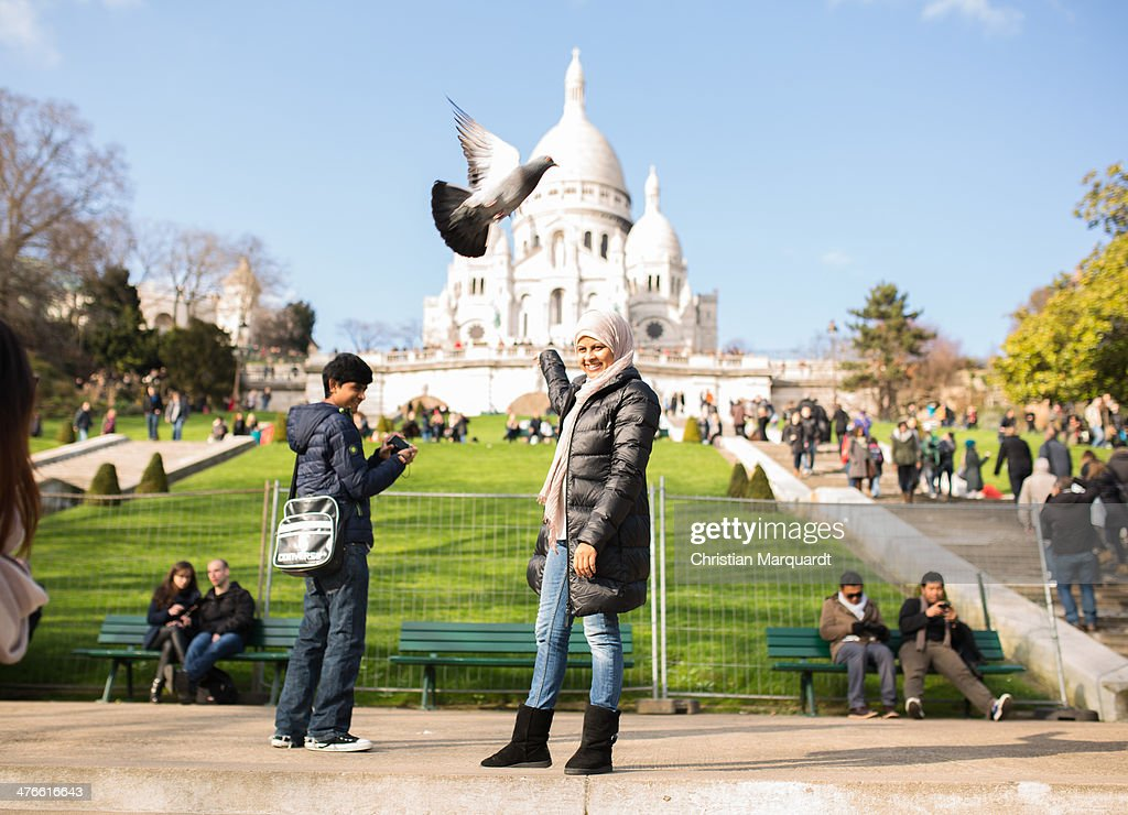 Tourists visit the Basilica Sacre-Coeur on a sunny day on March 1, 2014 in Paris, France. Sacre-Coeur is located on a hill named Montmatre which is also the name of the northern Parisian district.
