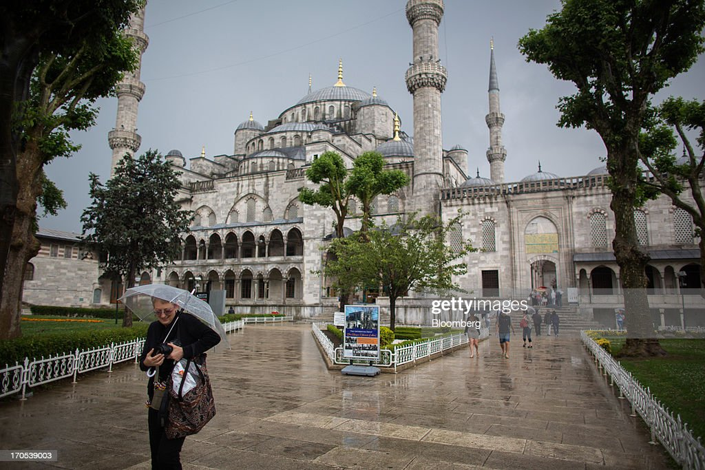 Tourists visit the Blue Mosque, also known as the Sultan Ahmed, in Istanbul, Turkey, on Friday, June 14, 2013. The law forbids the sale of alcohol at night and near schools and mosques, going against the secular traditions of the Muslim-majority country of 74 million, where many people drink and women often choose not to cover their hair. Photographer: Lam Yik Fei/Bloomberg via Getty Images