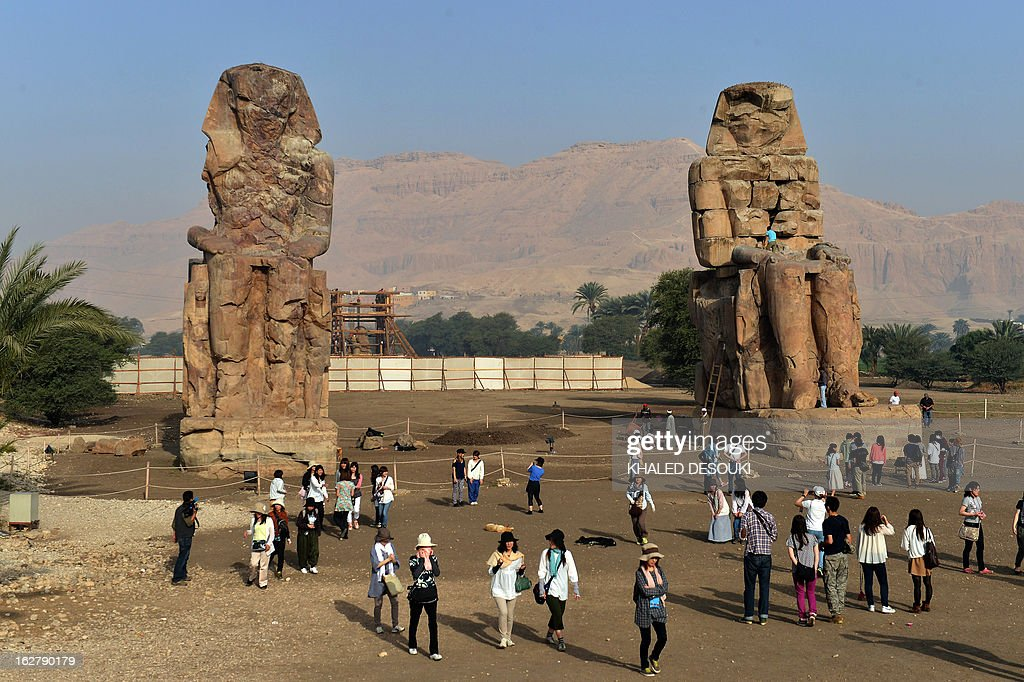 Tourists visit the Colossi of Memnon statues on February 27, 2013, in Egypt's ancient temple city of Luxor.