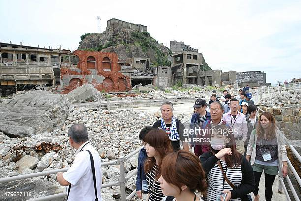 Tourists visit the Hashima coal mine known as 'battleship island' in Nagasaki prefecture Japan's southern island of Kyushu on July 6 2015 The UNESCO...