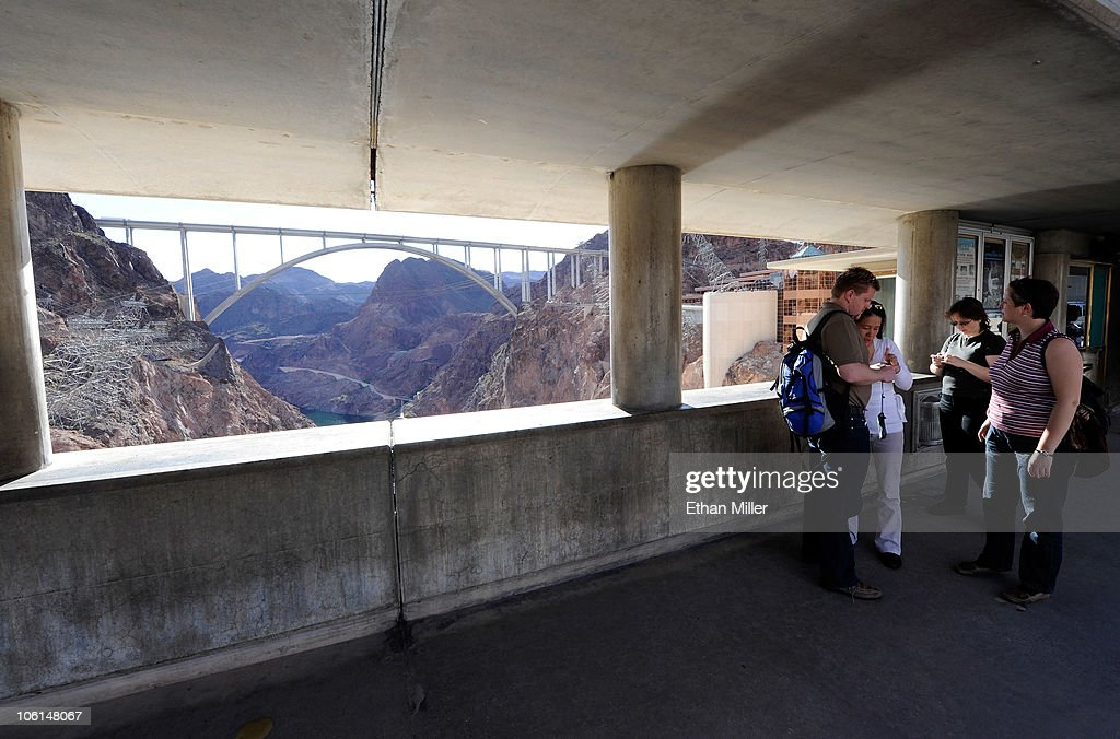 Tourists visit the Hoover Dam with the Mike O'Callaghan-Pat Tillman Memorial Bridge part of the Hoover Dam Bypass Project visible in the background October 26, 2010 in the Lake Mead National Recreation Area, Nevada. The 1,900-foot-long structure sits 890 feet above the Colorado River, about a quarter of a mile downstream from the Hoover Dam. The USD 240 million four-lane bypass project to relieve vehicle traffic on the Hoover Dam began in 2003, and opened to traffic on October 19.