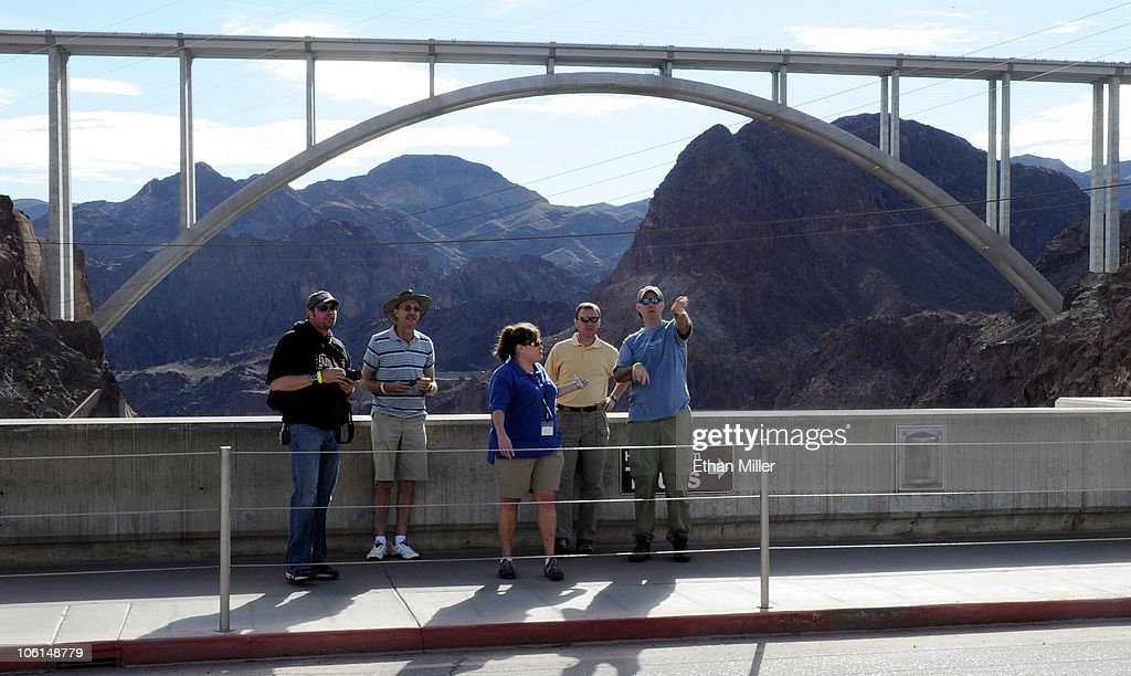 Tourists visit the Hoover Dam with the Mike O'Callaghan-Pat Tillman Memorial Bridge part of the Hoover Dam Bypass Project in the background October 26, 2010 in the Lake Mead National Recreation Area, Nevada. The 1,900-foot-long structure sits 890 feet above the Colorado River, about a quarter of a mile downstream from the Hoover Dam. The USD 240 million four-lane bypass project to relieve vehicle traffic on the Hoover Dam began in 2003, and opened to traffic on October 19.