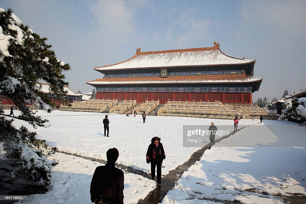 Tourists visit the Imperial Ancestral Temple following overnight snowfall on March 20, 2013 in Beijing, China. Beijing witnessed a heavy spring snowfall with a depth reaching 10-17 centimeters overnight.