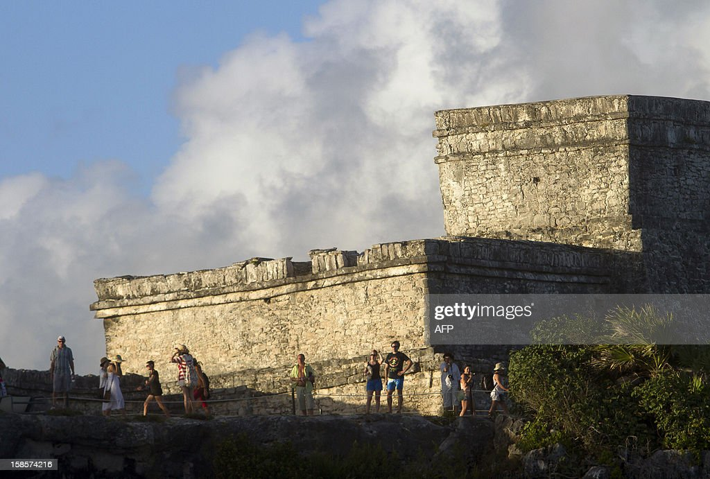 Tourists visit the Main Castle at Tulum archaeological park, 130 km south of Cancun, Mexico on December 19, 2012. Mexico is one of five countries preparing to celebrate on December 21, the end of the Maya Long Count Calendar --Baktun 13-- which began in 3114 BC. AFP PHOTO/Pedro Pardo