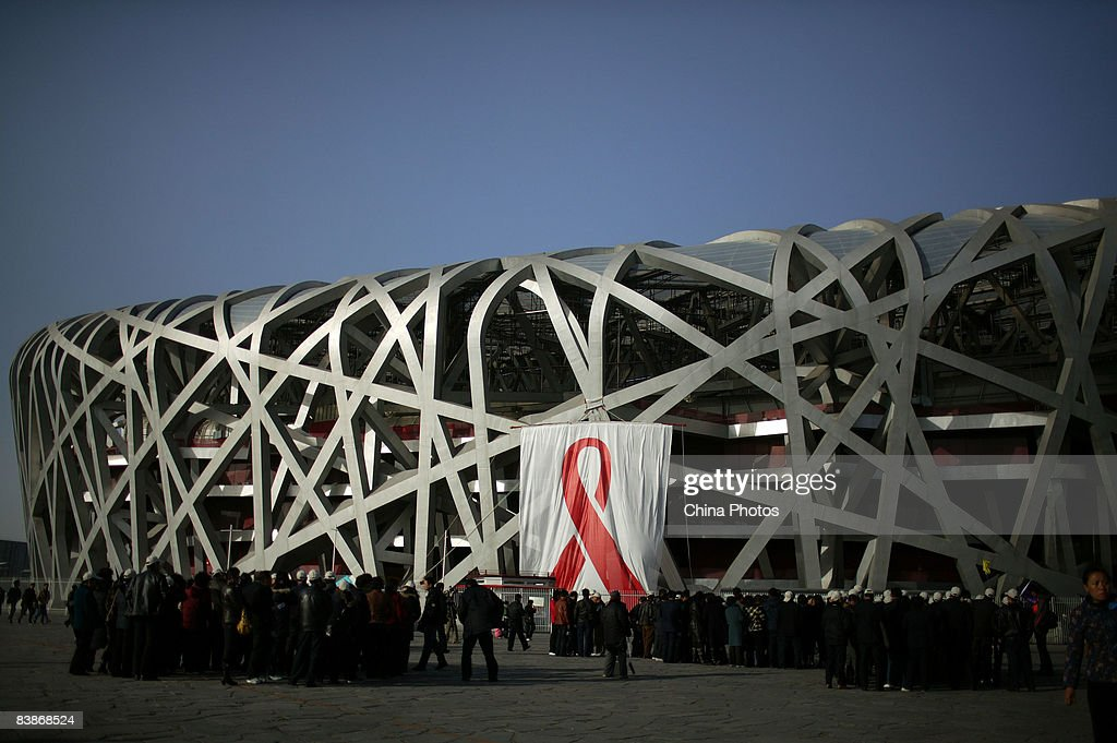 Tourists visit the National Stadium, dubbed the 'Bird's Nest', where five huge banners featuring the red ribbon are put up to mark the World AIDS Day on December 1, 2008 in Beijing, China. The banner each measures 20 meters (approximately 65.6 feet) high, 17 meters (approximately 55.76 feet) wide. According to official estimates, China has 700,000 people living with HIV with an estimated 85,000 with AIDS.