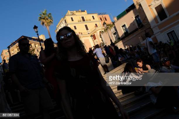 Tourists visit the Piazza di Spagna and the Spanish Steps in Rome on August 14 2017 at sunset / AFP PHOTO / Alberto PIZZOLI