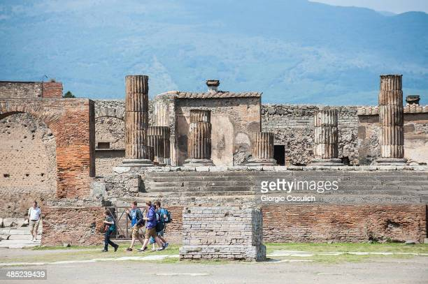 Tourists visit the ruins of the 'Tempio di Giove' at the archeological site on April 12 2014 in Pompei Italy The Italian government has enacted a...