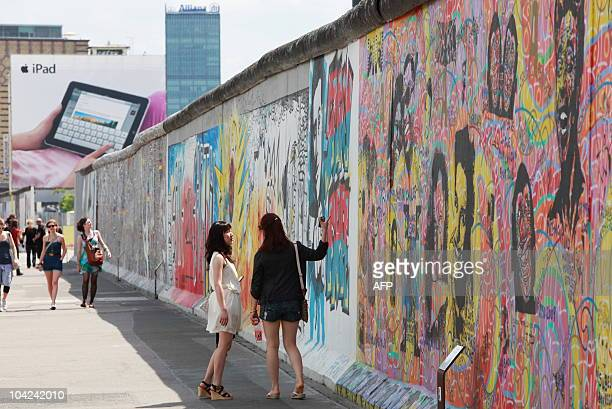 Tourists visit the section of the Berlin Wall at the Eastside gallery in front of a giant billboard featuring Apple's new iPad as the sun shines in...